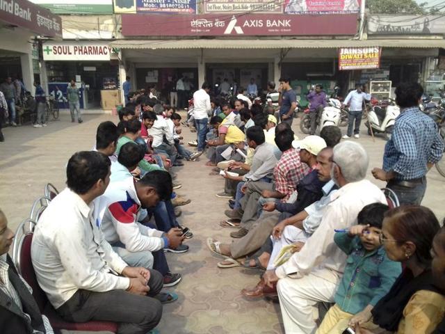 People wait outside an Axis Bank branch in Noida.(Mohd Zakir/HT Photo)