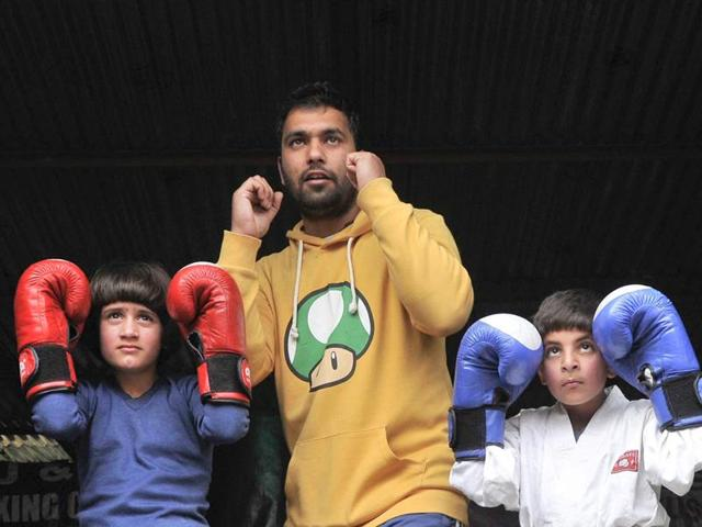 Kickboxers Tajamul Islam (left) and Hashim Peerzada (right) with their coach Faisal Ali at the academy in Bandipora.(Waseem Andrabi/HT Photo)