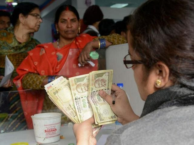 A bank employee counts notes as people gather inside a bank to deposit Rs 500 and Rs 1000 notes at a bank in Amritsar on Friday.