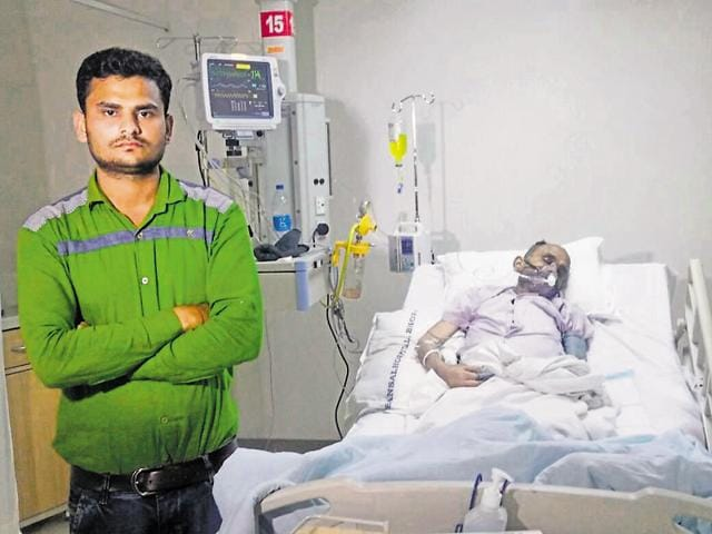 Amit Gupta (green shirt) with his father Harikrishna, who is in need of a liver transplant, in a Bhopal hospital.