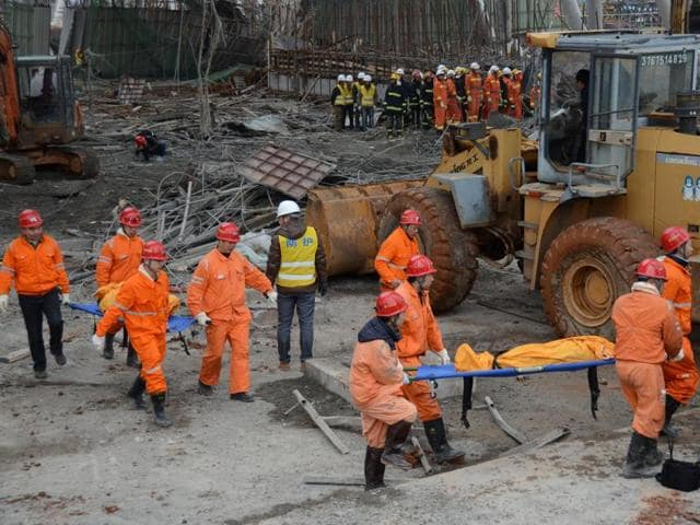 Workers search for survivors in the debris of a collapsed platform in a cooling tower at a power station at Fengcheng, in China's Jiangxi province.