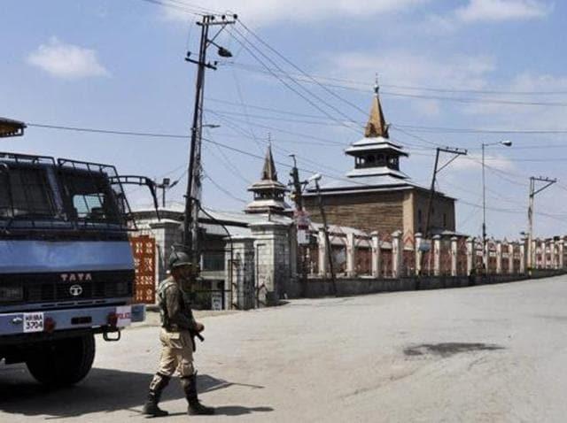 A security jawan stands guard on a deserted street near Jamia Masjid in Srinagar.