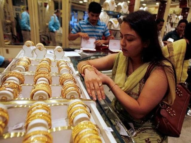 A woman tries on a gold bracelet at a jewellery showroom in the eastern Indian city of Siliguri November 4.