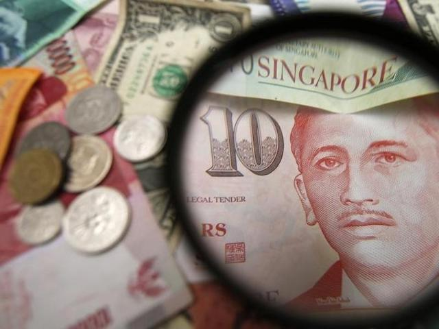 Singapore currency notes are seen through a magnifying glass among other currencies in this photo illustration.