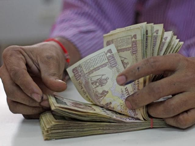 A man counts old Rs 500 notes in a bank at Vashi in Mumbai on Tuesday.