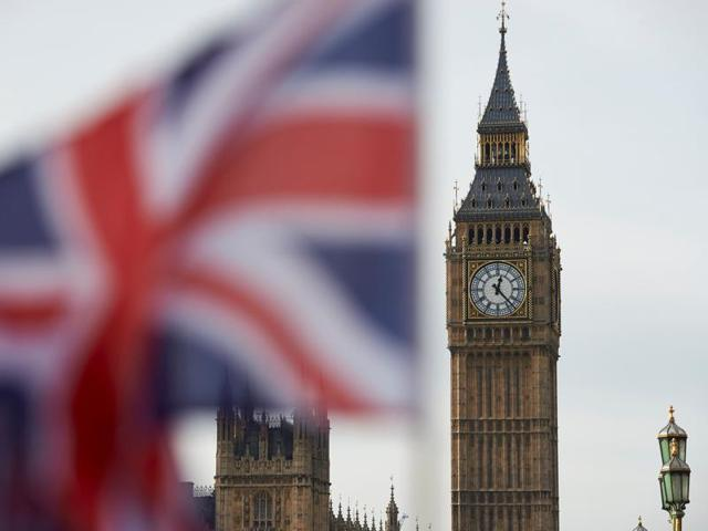 A Union flag flies in the wind in front of the Big Ben clock face and the Elizabeth Tower at the Houses of Parliament in central London.