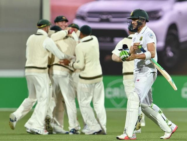 South Africa captain Faf du Plessis (R) walks back to the pavilion as Australia's players celebrate after dismissing him during the third day of the third Test at the Adelaide Oval on Saturday.