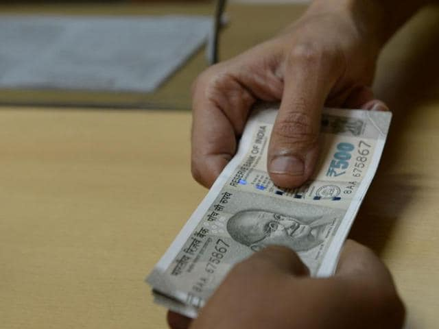 A bank staff member hands Indian 500 rupee notes to a customer in Mumbai.