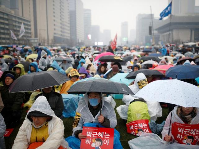 A man carrying his child on his shoulder attends a protest calling for Park Geun-hye to step down in central Seoul.