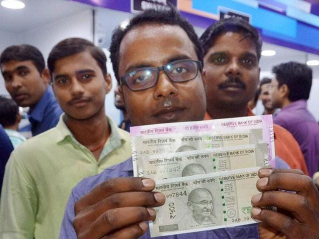 A man shows Rs 500 and Rs 2000 notes after withdrawing them from an ATM in Patna on Tuesday.
