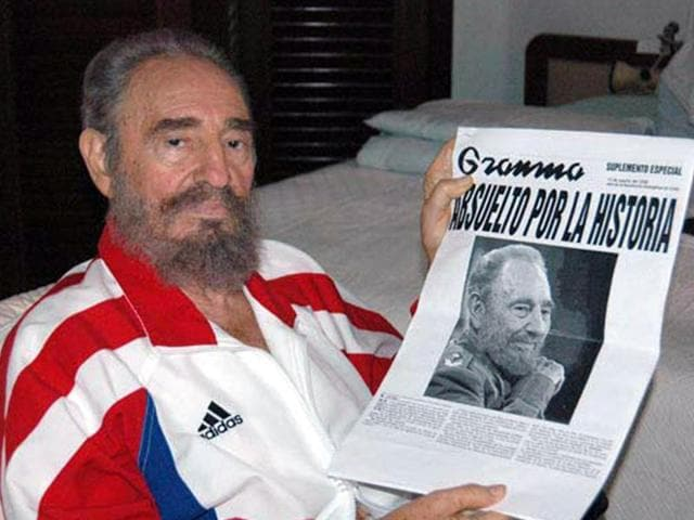 Cuban President Fidel Castro shows a copy of a newspaper in this August 13, 2006 file photo.