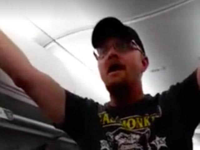 The video shows the man standing in the aisle, yelling and insulting Hillary Clinton supporters.