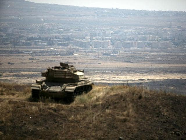 The Syrian area of Quneitra is seen in the background as an out-of-commission Israeli tank parks on a hill, near the ceasefire line between Israel and Syria, in the Israeli-occupied Golan Heights.