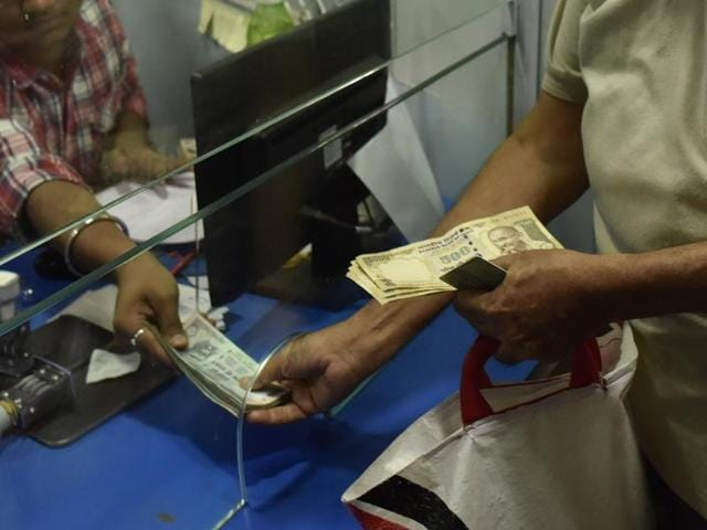 A man gets his old 500 rupees notes exchanged with 100 rupees at a bank in Mumbai.