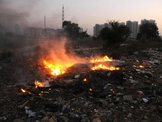 Waste burning in open area in Sector 49.(Parveen Kumar/HT)
