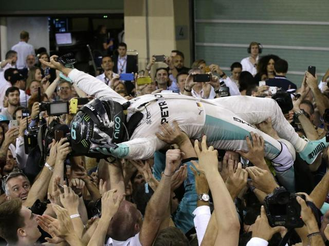 Mercedes driver Nico Rosberg celebrates after winning the 2016 Formula One title at the Yas Marina racetrack in Abu Dhabi.(AP)