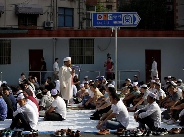People sit before the start of prayers for the Muslim holiday of Eid Al-Adha on a street outside a mosque in Shanghai, China.