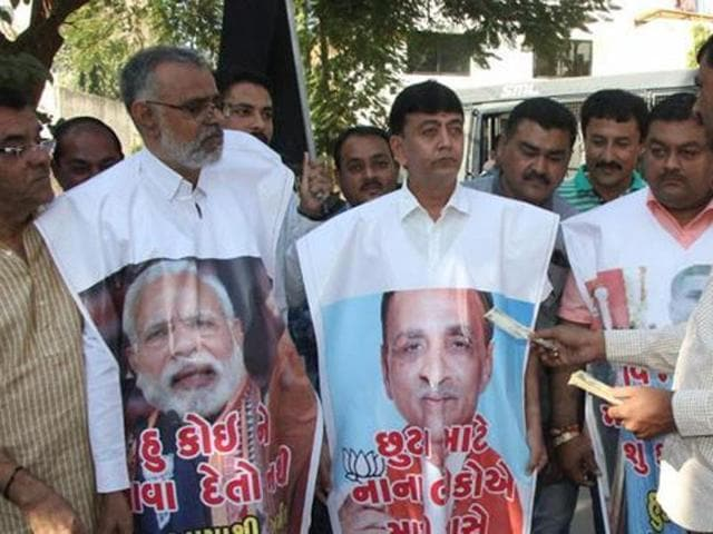 Congress supporters protest against Prime Minister Narendra Modi over the ban on Rs500 and Rs1,000 notes outside Gujarat chief minister Vijay Rupani's house in Rajkot on Sunday.