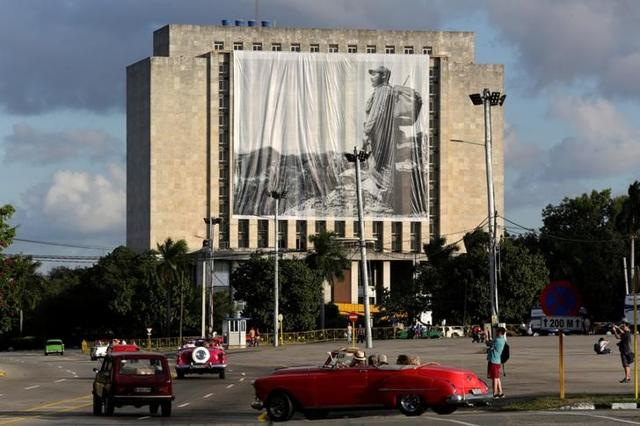 A picture of Cuban former president Fidel Castro hangs in front of the Cuban National Library at Revolution Square in Havana, Cuba.