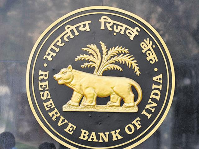 Passers by are reflected on the logo of the Reserve Bank of India (RBI) outside its headquarters in Mumbai.