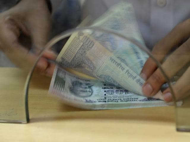 A customer counts Indian 100 rupee currency notes after withdrawing money at a bank on November 24  in Mumbai.