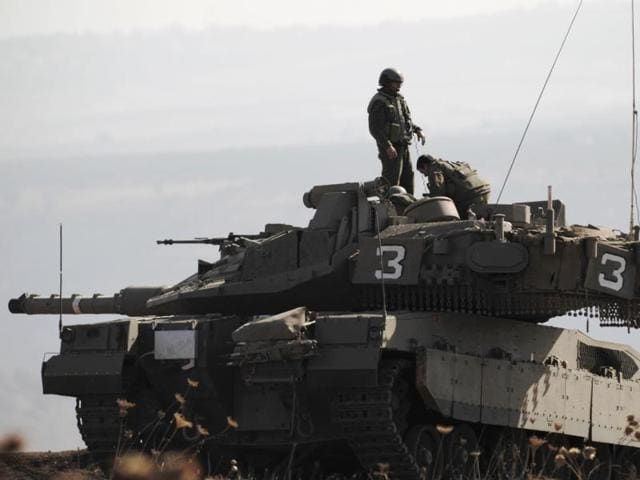 Israeli soldiers on a tank monitor the area near the Israel-Syria border in the annexed Golan Heights, following an attack by gunmen linked to the Islamic State group.