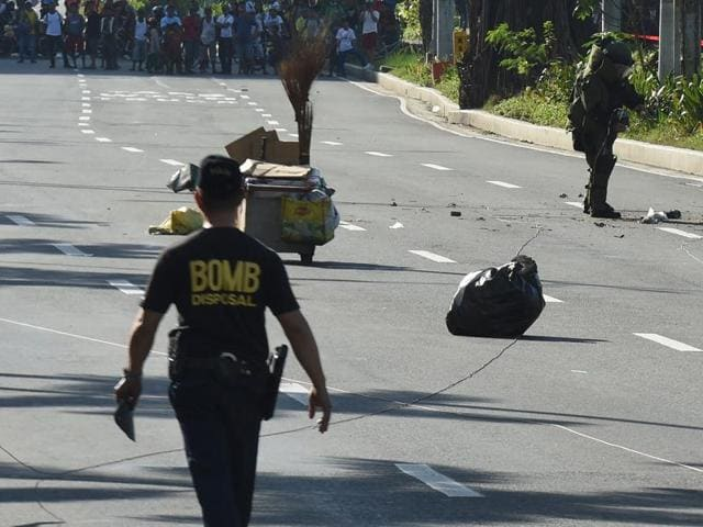 A member of police bomb disposal unit holding a water bomb disruptor, walks towards the site where a suspicious package was found, for detonation along Roxas boulevard near the US embassy in Manila on Monday.