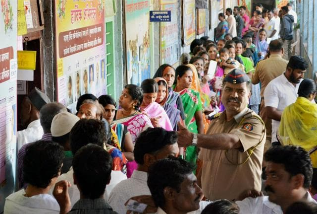 Voters standing in a queue to cast their votes at a polling booth for Municipal Council Elections in Karad on Sunday.(PTI Photo)