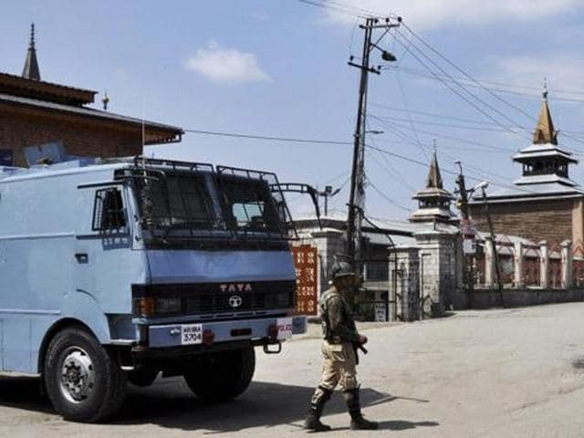 In this file photo, a security jawan stands guard on a desterted street near Jamia Masjid in Srinagar.