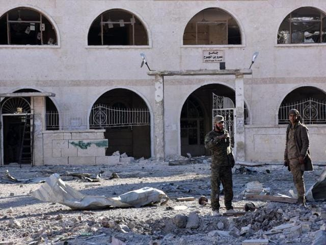 Syrian pro-government forces inspect an area on November 27 in eastern Aleppo, a day after they reseized it from rebel fighters.