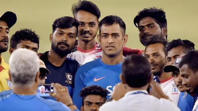 Mahendra Singh Dhoni with local bowlers at a practice session at Barabati Stadium in Cuttack.