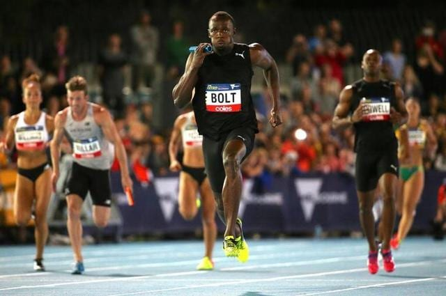 Usain Bolt runs after receiving the baton from teammate and compatriot Asafa Powell during the final night of the Nitro Athletics series at the Lakeside Stadium in Melbourne, Australia on Saturday. (Reuters)