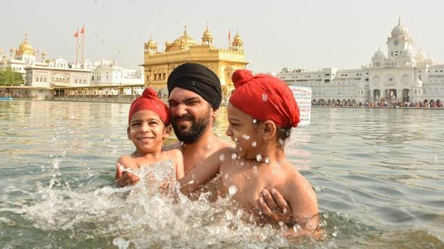 Devotees taking holy dip and paying obeisance at Golden Temple on the occasion of martyrdom anniversary of Sikh Guru Arjan Dev in Amritsar on Monday.