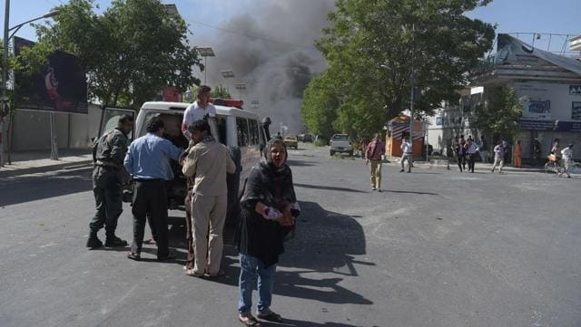 A wounded Afghan woman (C) looks on after receiving first aid at the site of a car bomb attack in Kabul .