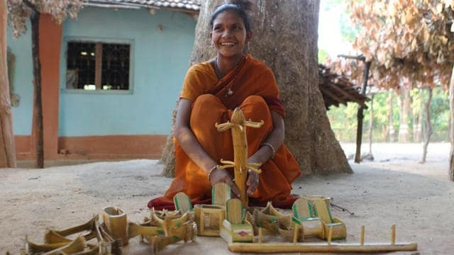 A tribal woman shows off finished bamboo products such as home furnishings and toys at the Mendha Lekha village, Gadhchiroli, Maharashtra