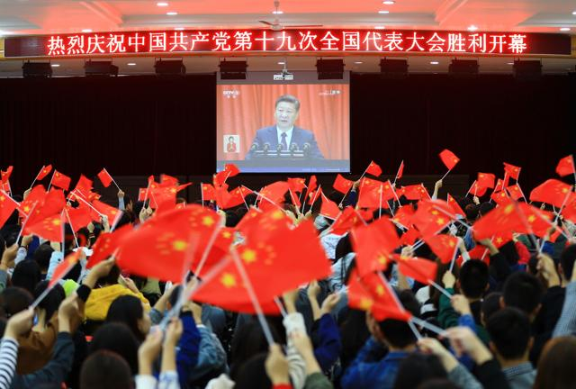 College students wave national flags as they watch the opening of the 19th Communist Party Congress in Huaibei in Chinas eastern Anhui province on October 18, 2017. (AFP)
