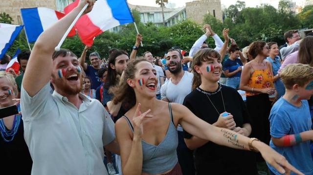 French and Lebanese football fans watch the World Cup final between France and Croatia in the garden of French cultural center in the capital Beirut.