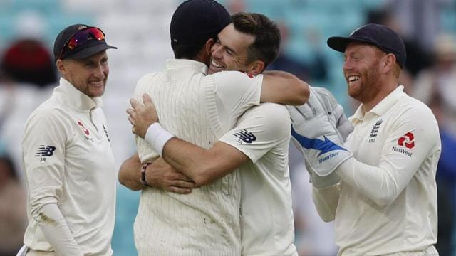 England's James Anderson (C) celebrates with England's Alastair Cook after taking the wicket of India's Mohammed Shami.