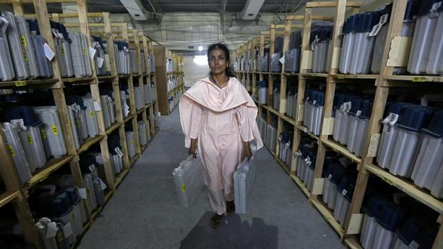 An election staff member carries Electronic Voting Machines (EVM) after collecting them from a distribution centre at an indoor stadium ahead of the seventh and last phase of general election, in Kolkata, West Bengal.