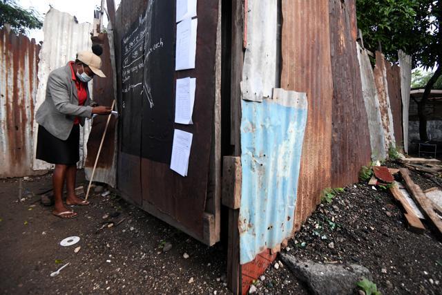 Educator Taneka Mckoy Phipps writes a lesson on a makeshift blackboard. (REUTERS)