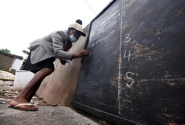 Educator Taneka Mckoy Phipps writes a lesson on a blackboard painted on a zinc fence in Jamaica. (REUTERS)