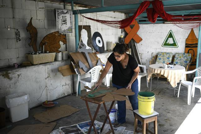 La artista Susan Applewhite pinta su diseño en una caja de cartón reciclado en su casa en Caracas, Venezuela.  (Abi)