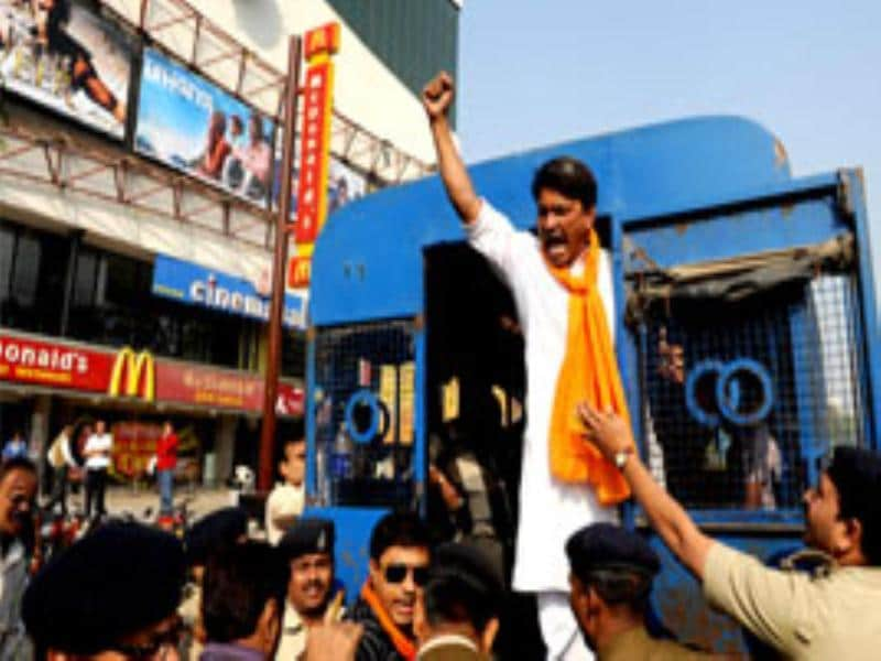 A supporter from the VHP and Bajrang Dal shouts slogans from the police van after being arrested by the police during a protest outside the City Gold Multiplex screening My Name is Khan starring Shah Rukh Khan in Ahmedabad.