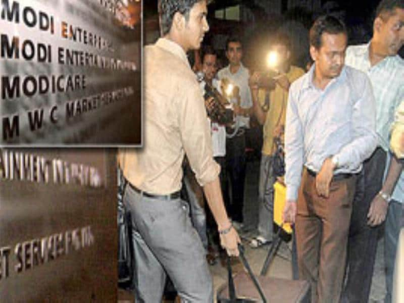 A combo picture shows Income Tax officials carrying a bag while entering IPL Commissioner Lalit Modi's office in Mumbai.