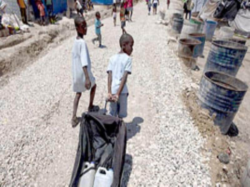 Two boys take turns using an old roller suitcase to transport water inside a camp for displaced people in Port-au-Prince.