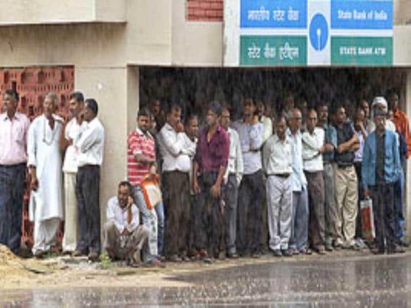 People take shelter outside an automated teller machine as it rains in Gandhinagar