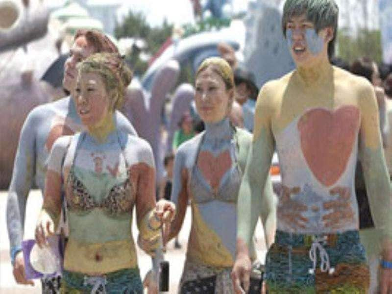 Tourists with their bodies painted with coloured mud stroll during the Boryeong Mud Festival on Daecheon Beach in Boryeong , South Korea.