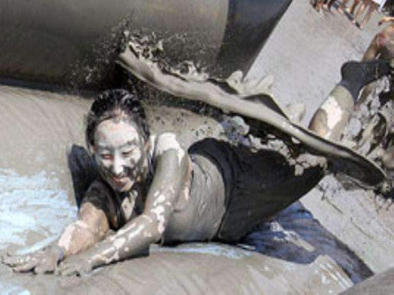 A woman slides as an event personnel pours mud during the 14th Boryeong Mud Festival at Daecheon beach in Boryeong, about 190 km southwest of Seoul.