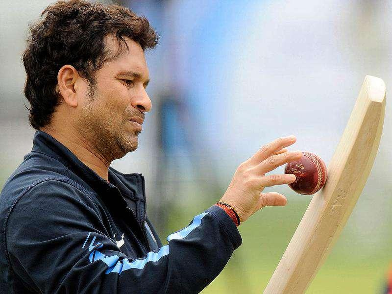 Sachin Tendulkar throws a ball against a bat during a training session before the first cricket test match against England at Lord's cricket ground in London.