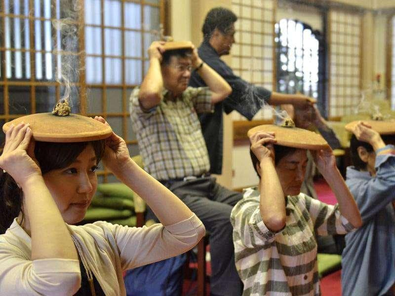 Buddhists burn moxa (dried medicinal herbs) atop unglazed pottery plates over their heads as they pray for good health during a traditional summer ritual at Tokyo's Myoenji temple. The 350-year-old custom called 'houroku-kyu' is believed to keep heads cool and refresh bodies.